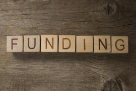 text FUNDING on a wooden background